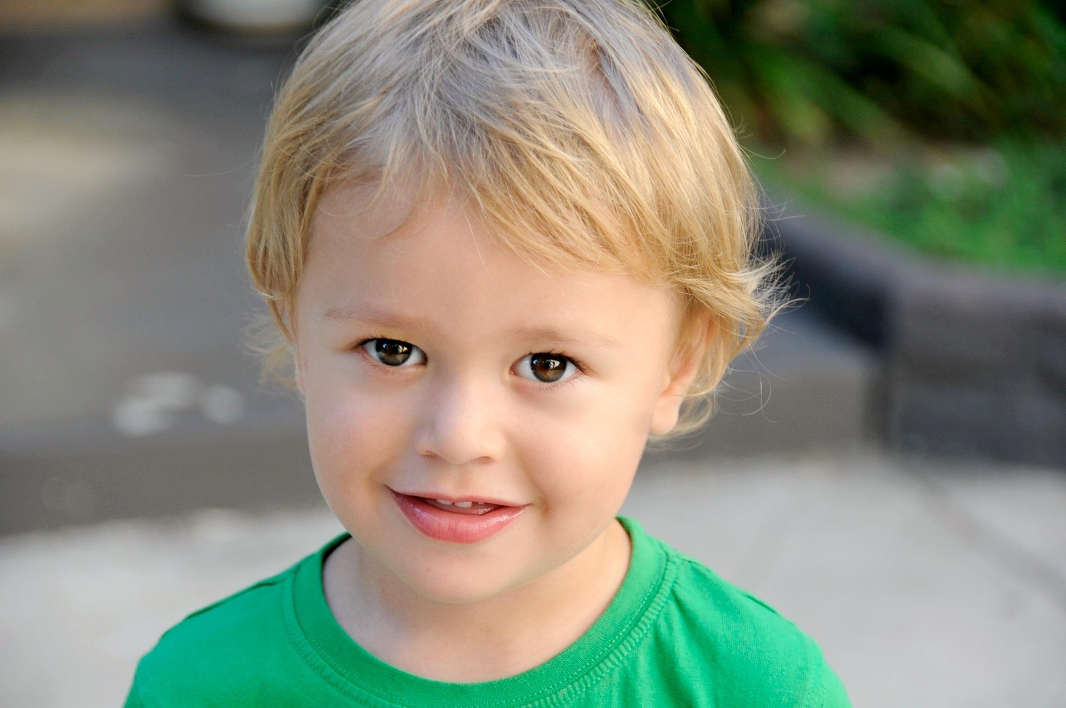 smiling boy in green