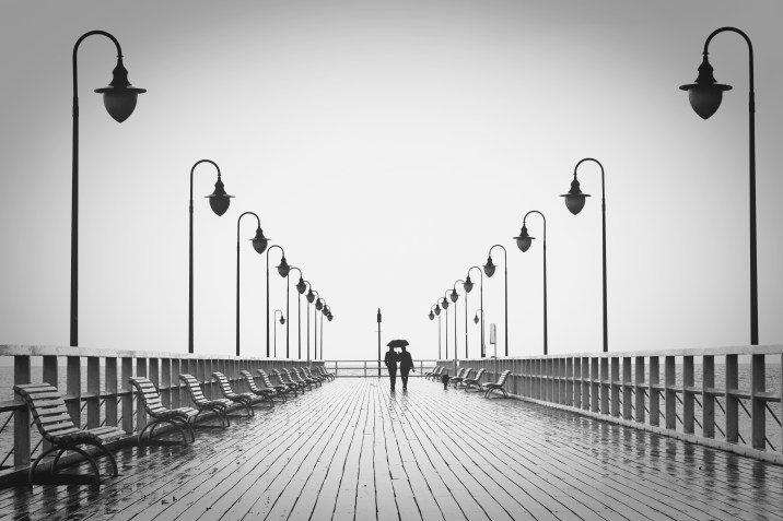 Two People Walking on Pier