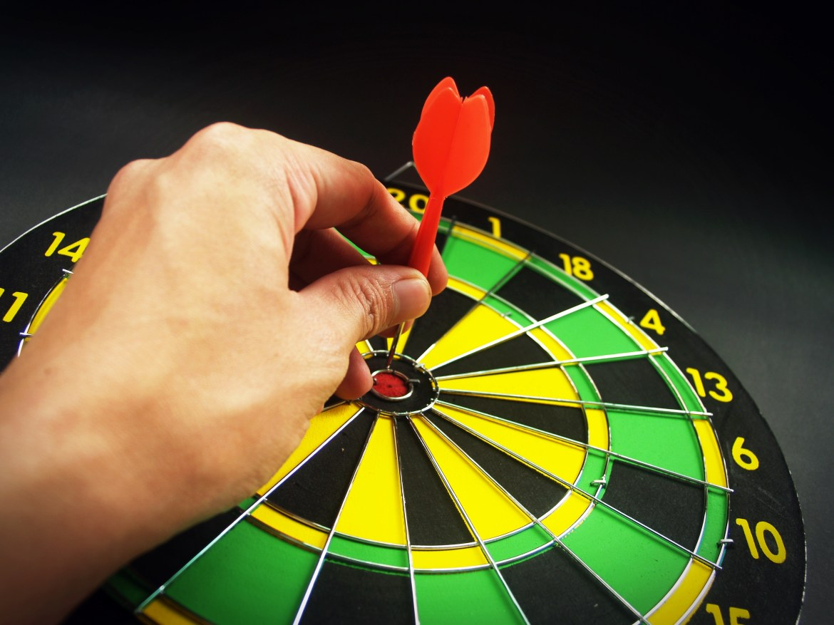 Person Holding Red Dart on Green Yellow and Black Dart Board