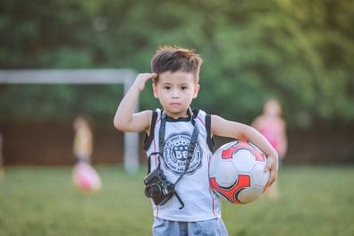 Saluting Boy Wearing White Top Holding Camera