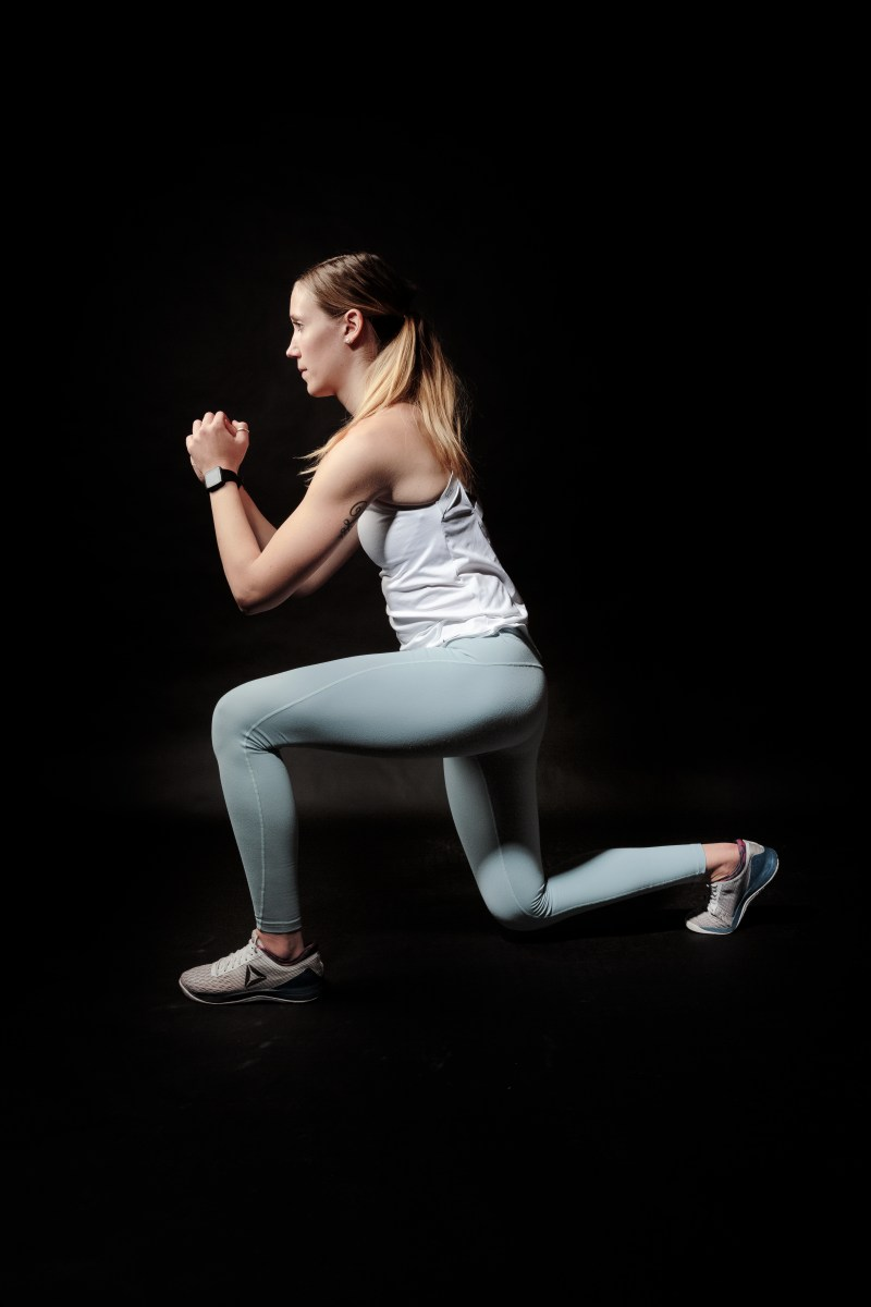 Side View Photo of Woman Doing Lunges Against Black Background