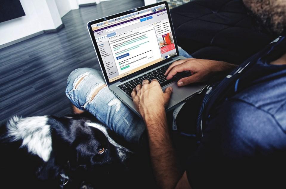 Man Sitting While Using Laptop Inside House