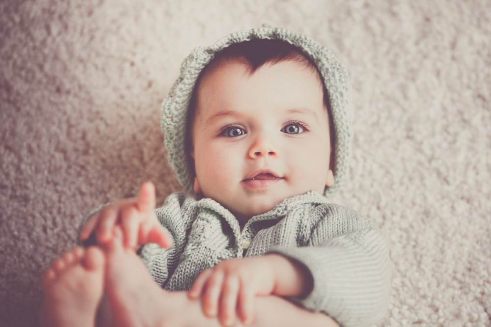 Baby on Gray Knit Hooded Clothes Lying on Carpet