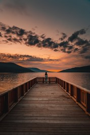 Wooden pier against mountains and sunset sky