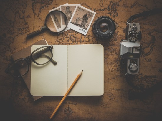 Silver Dslr Camera Beside Book