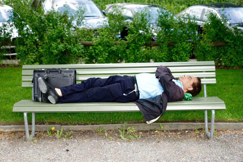 Man Sleeping on Gray Bench