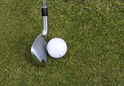 Silver Wedge Golf Club Beside Ball