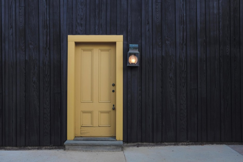 Closed Door and Lighted Light Sconce  Free Stock Photo