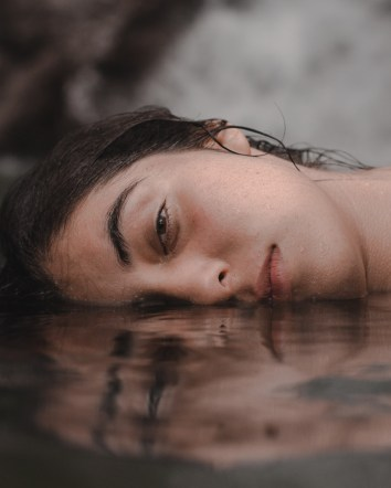 woman half cheek submerge on water