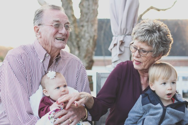 Grandmother and Grandfather Holding Child on Their Lap