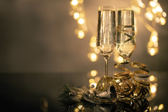 Close-Up Of Two Flute Glasses Filled With Sparkling Wine Wuth Ribbons And Christmas Decor