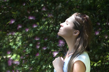 Woman Closing Her Eyes Against Sun Light Standing Near Purple Petaled Flower Plant