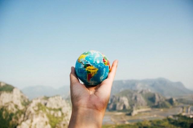Person Holding World Globe Facing Mountain gaia