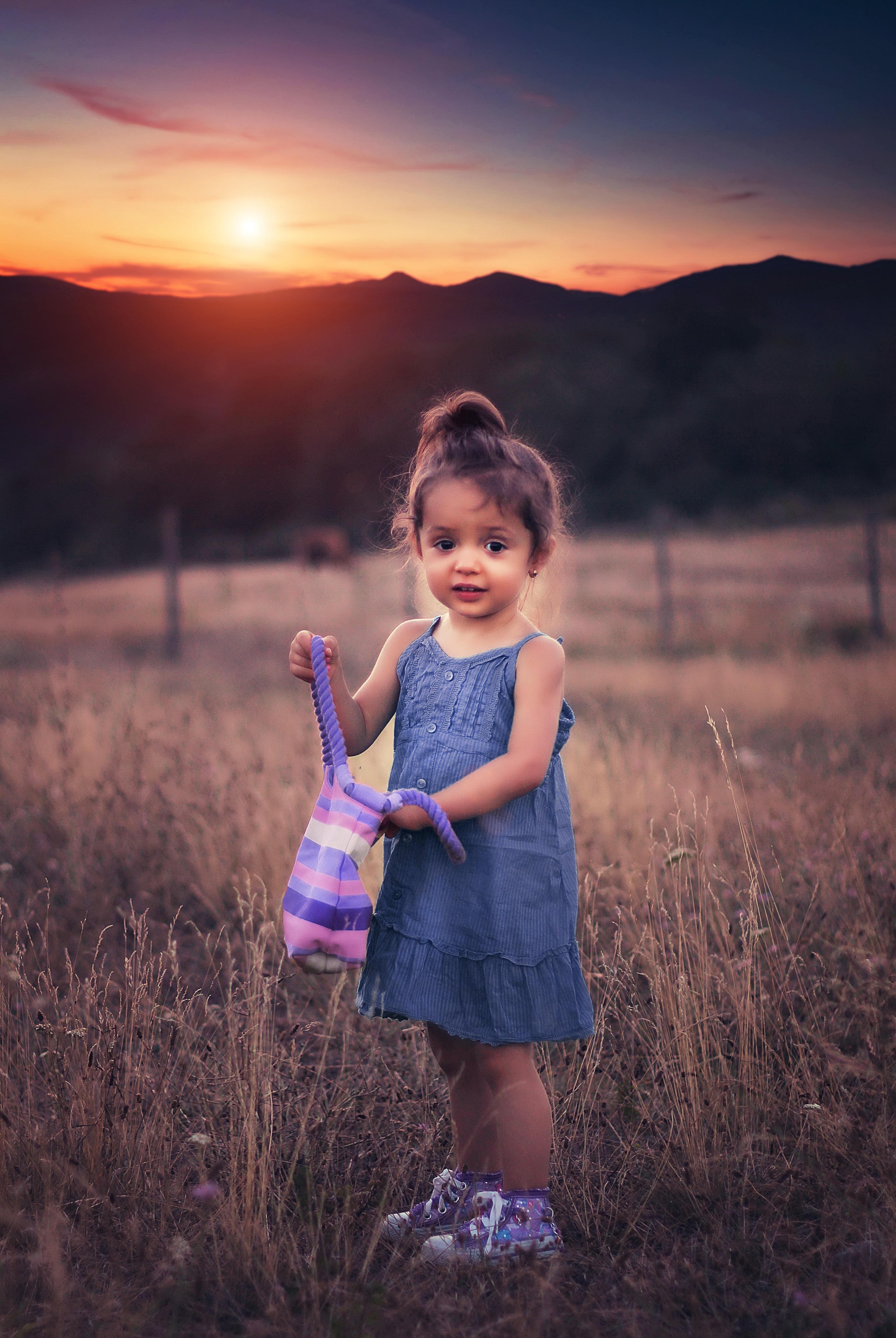Cute Baby Girl Swing Hd Wallpaper Girl In Blue Dress Standing On Grass Field During Sunset