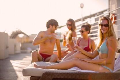 Amici Felici Che Bevono Gustose Bevande Mentre Prendono Il Sole Insieme Sulla Spiaggia Nella Soleggiata Giornata Estiva
