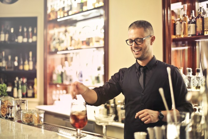 Happy young male barkeeper standing at counter and preparing alcohol cocktail for order while working in modern pub