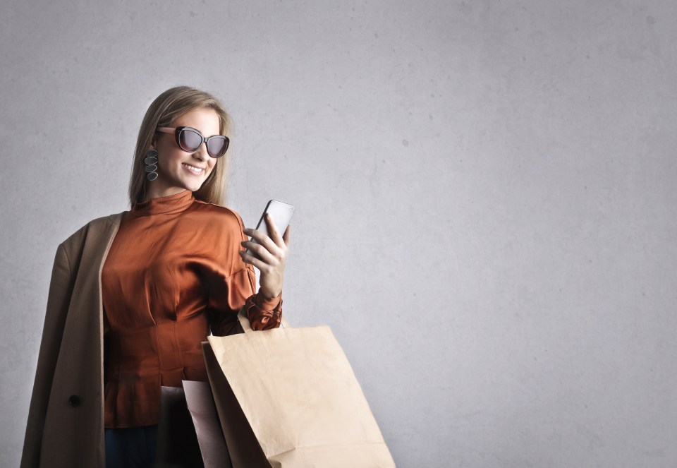 Stylish cheerful woman with shopping bags using smartphone