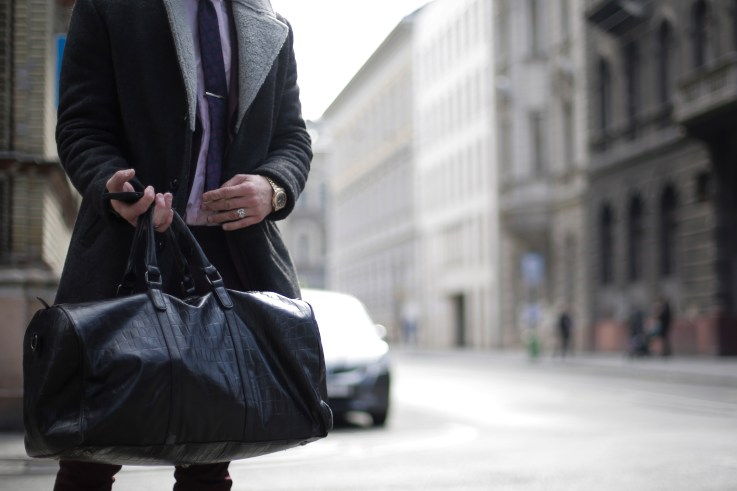Person in Black Trench Coat Holding Black Leather Travelbag