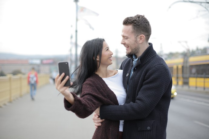 Positive young multiracial couple taking selfie while walking on street