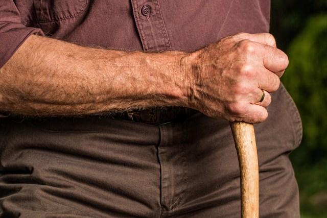man holding wood cane