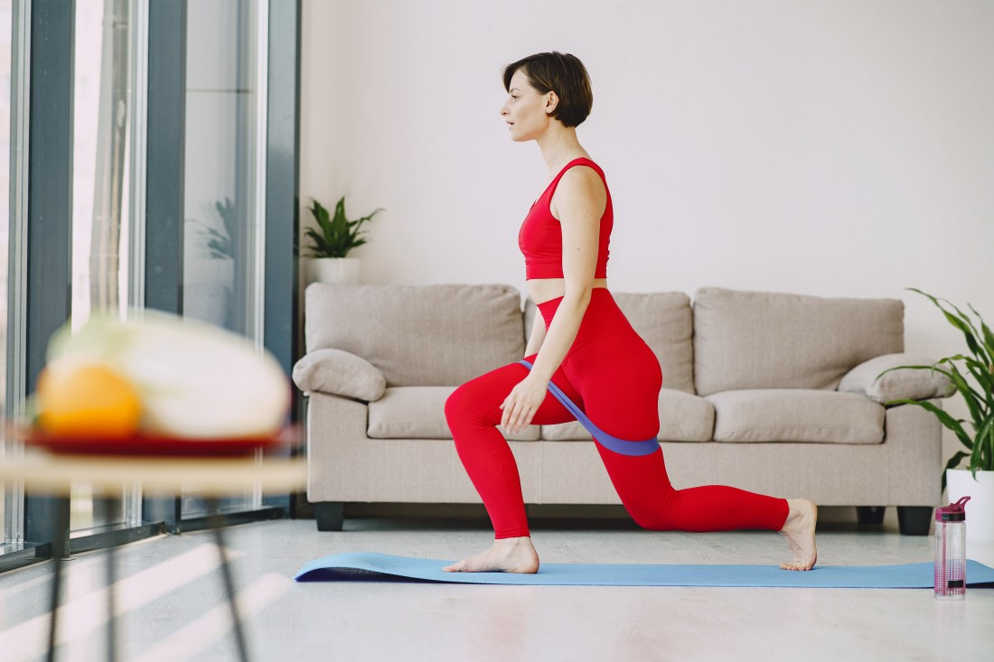 Sportswoman doing stretching exercise on mat