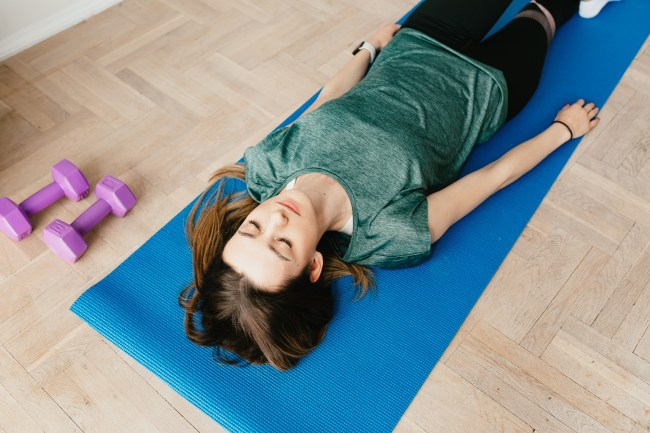 From above of young slender lady in casual clothes and wristwatch resting with closed eyes on blue yoga mat near dumbbells on floor in flat