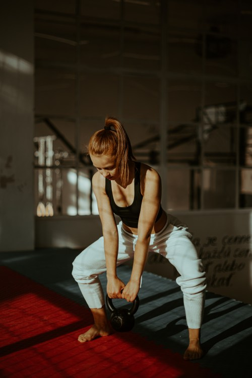 Sporty young woman squatting with kettlebell in studio