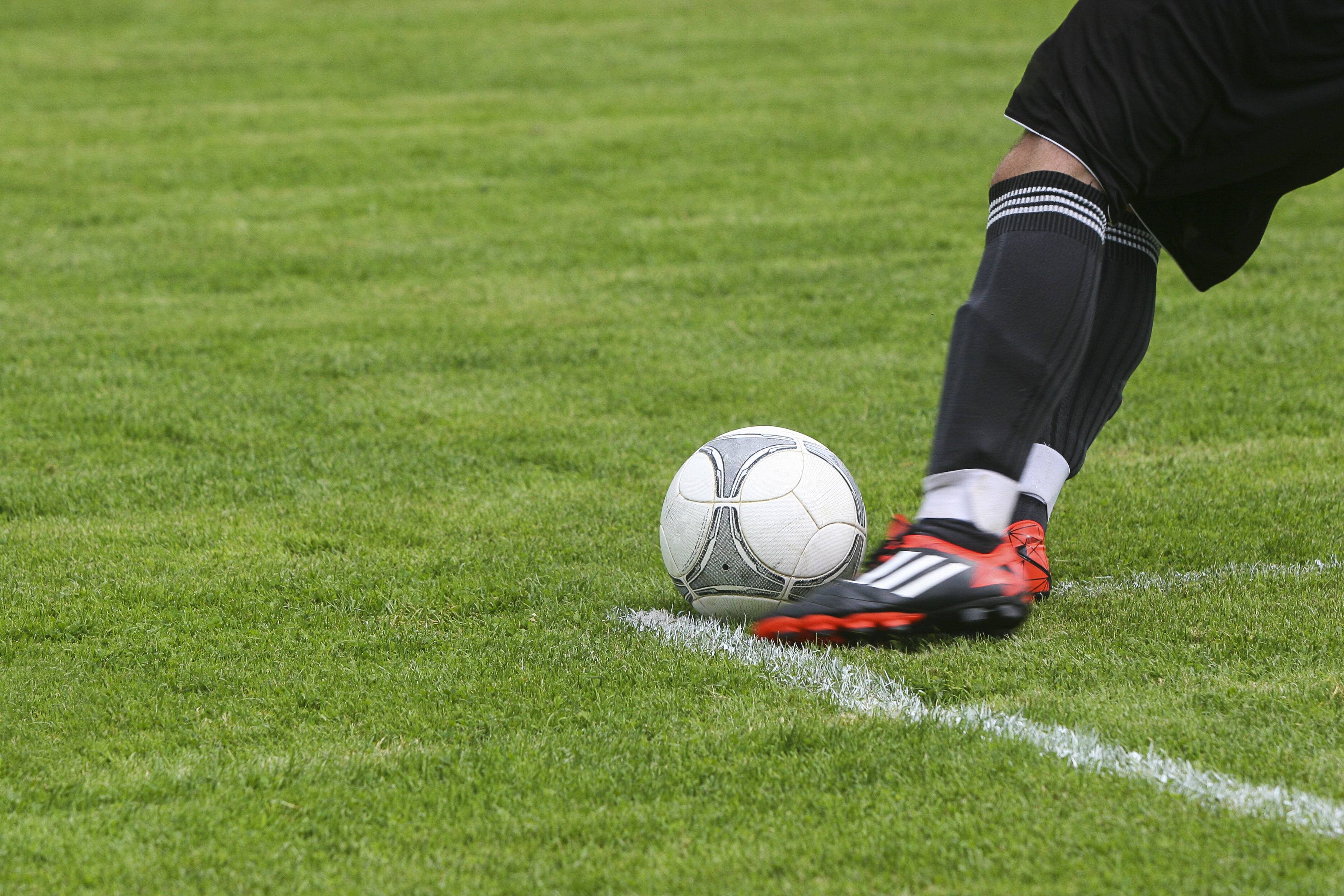Soccer Player Kicking White Gray Soccer Ball on Green Grass Field