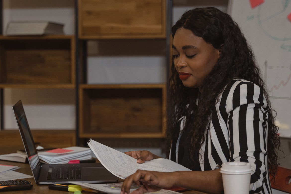 Woman in Black and White Stripe Shirt Reading a Book