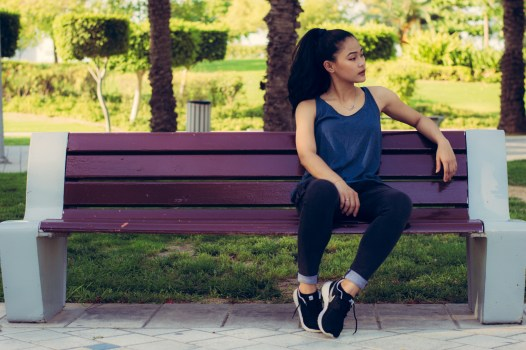 Man Sitting on Other Edge of Bench Parallel to Woman With Bags in Between Them  Free Stock Photo