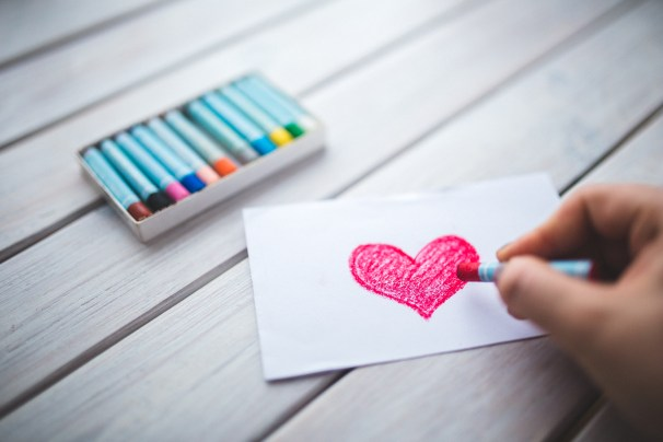 Hand with oil pastel draws the heart