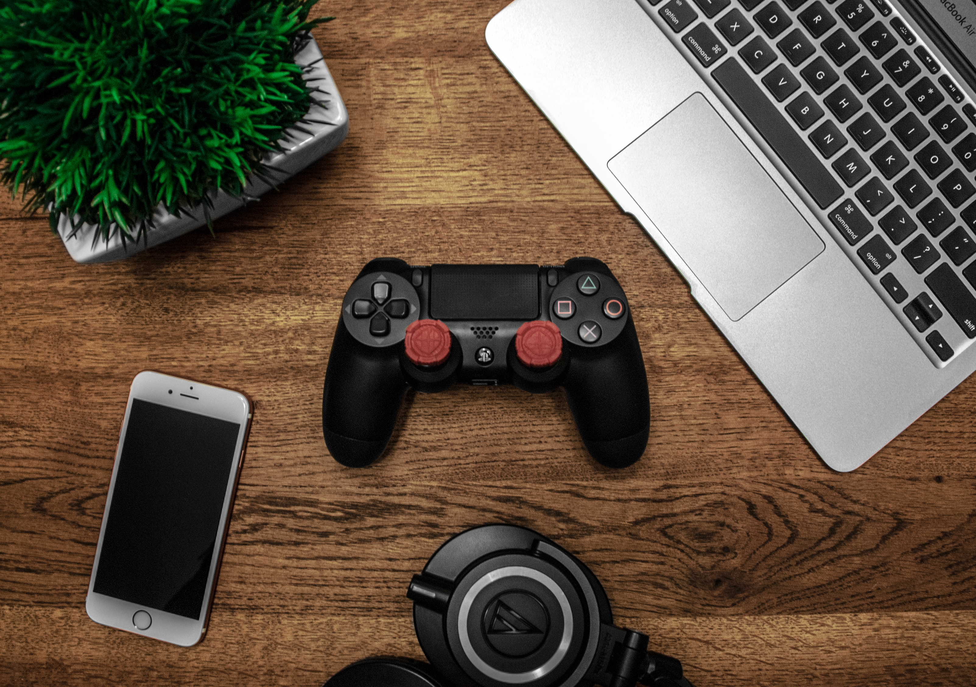 Silver Macbook Beside Black Sony Ps4 Dualshock 4 Silver