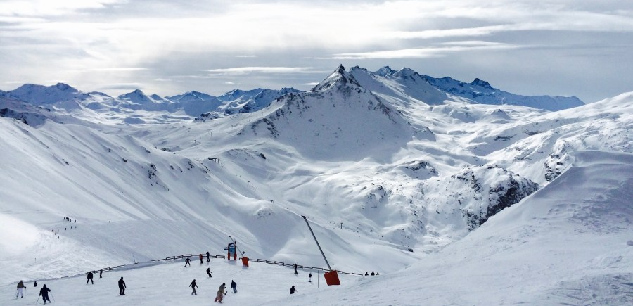 People Lurking Around on Snow Field Near Mountains