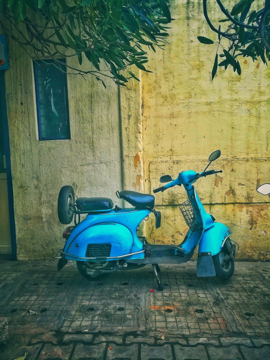 Teal Motor Scooter on Road