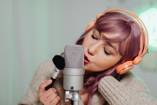 Woman in Gray Knit Sweater Holding Microphone