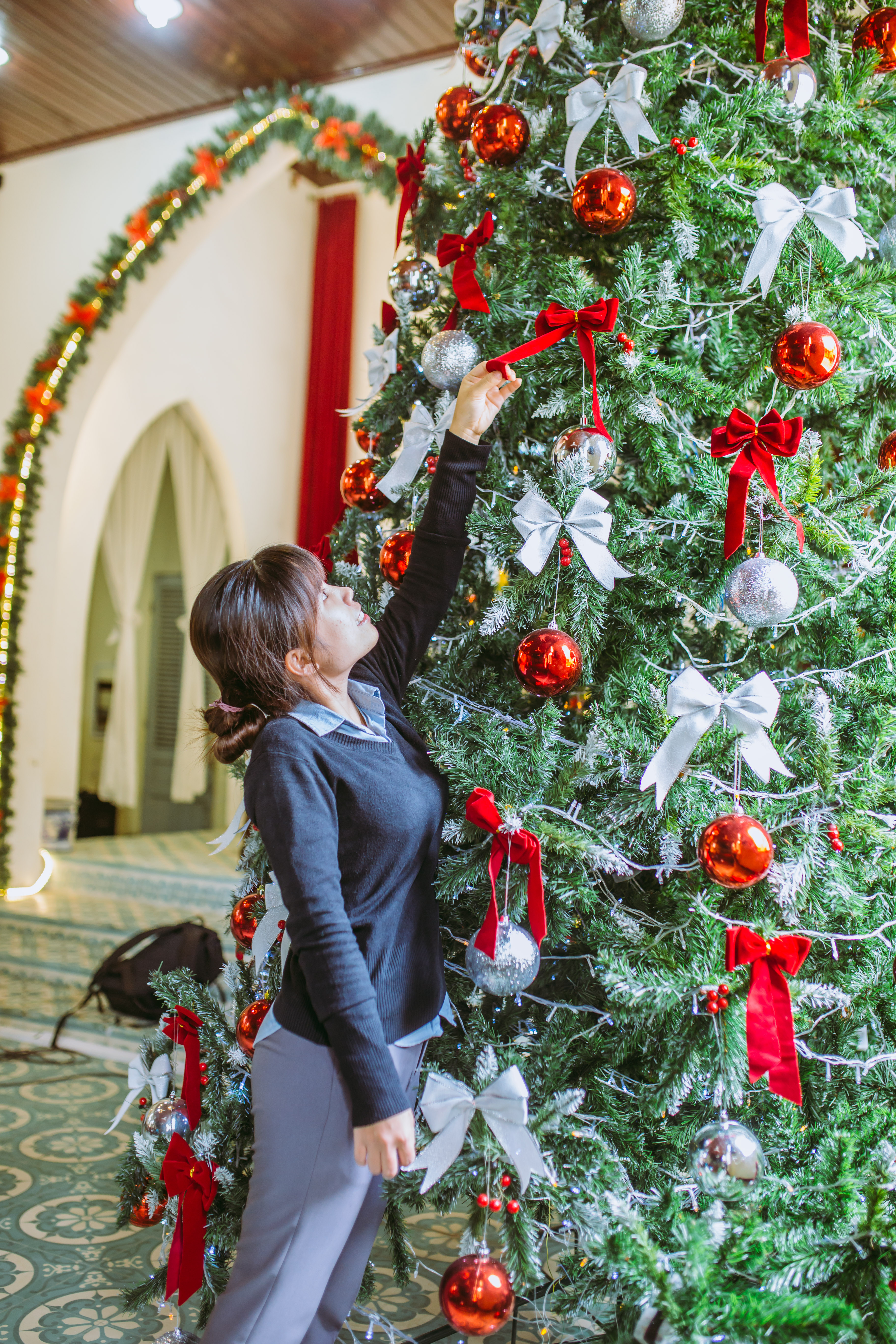 Woman Putting Ribbon Bow On Christmas Tree Free Stock Photo