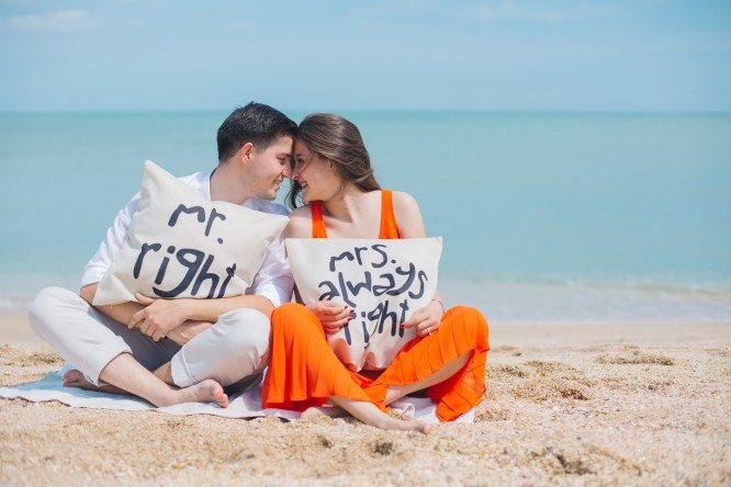 Man and Woman Wearing Cloths Sitting on Brown Sand Near Seashore
