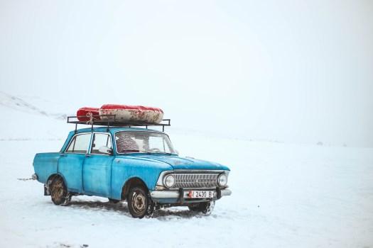 Sedán azul en la nieve en el día