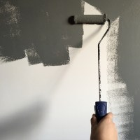 Person Holding Paint Roller While Painting the Wall  Free