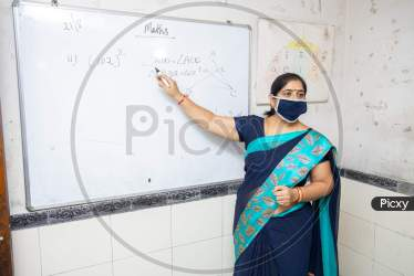 Image of Female Teacher Wearing Mask And Saree Teach Math On Whiteboard In Classroom Indian School Education Class During Covid19 Pandemic New Normal LI014503 Picxy