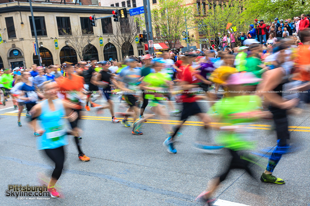 Runners blur past during the Pittsburgh Marathon