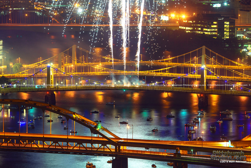 Fireworks shoot off of the Roberto Clemente Bridge with boats watching