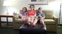 Barefoot Woman With Two Children Sit Couch And Watch Tv