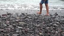 Detail Of Guy Legs Walking In Gravel Beach