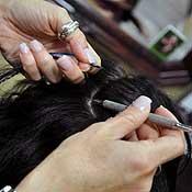 Gabrielle Aquaro attaches a feather hair extension