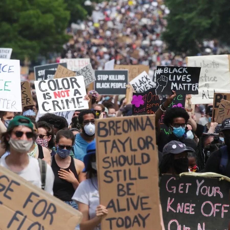 Une marée bigarrée de manifestants portant le masque et des pancartes occupent toute l'image.