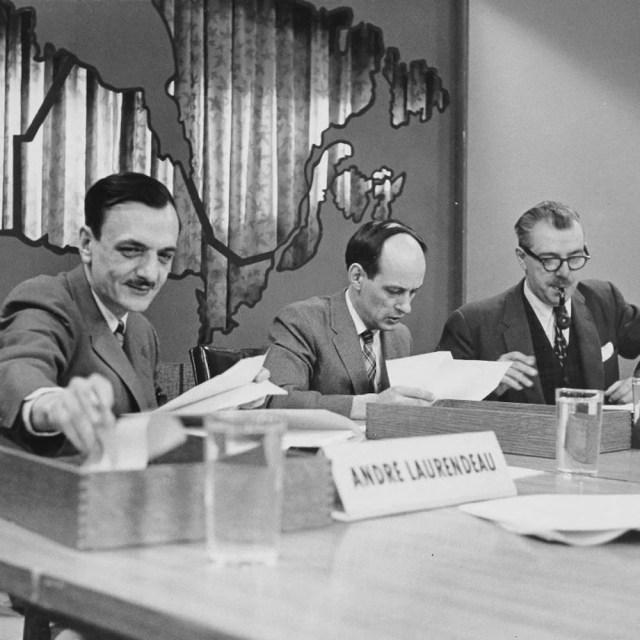 André Laurendeau, René Lévesque et Roger Duhamel consultant leurs notes sur un long bureau.