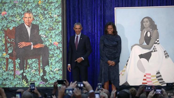 Barack et Michelle Obama prennent la pose, souriants, devant les portraits dévoilés à la National Portrait Gallery de Washington et pris en photo par de nombreuses personnes.