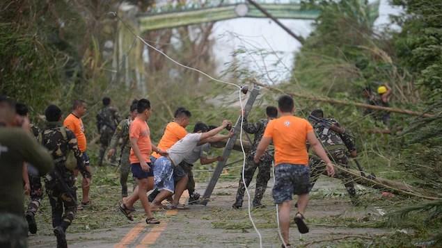 Des secouristes tentent de dégager la route, bloquée par des arbres et des poteaux d'électricité qui sont tombés sous les vents du super typhon Mangkhut.
