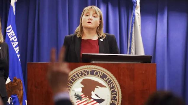 Une femme blonde d'âge moyen debout, écoutant la question d'un journaliste durant une conférence de presse.